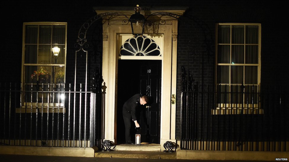 A lantern being placed at the front door of Number 10 Downing Street