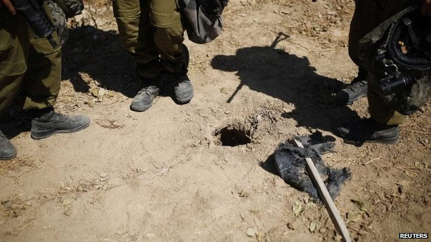 Israeli soldiers stand next to a hole in the ground they suspect is connected to a tunnel, outside the Gaza Strip August 10