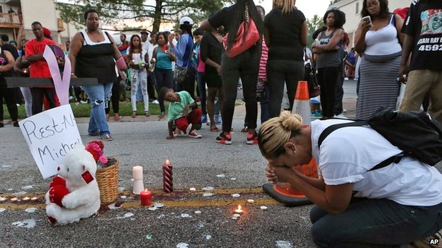 A woman prays at the spot where Michael Brown was killed on 10 August 2014 in Ferguson