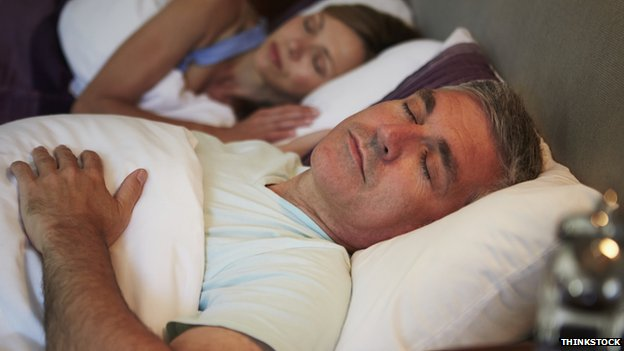 Two people asleep in bed, a man and woman