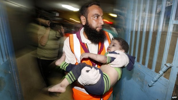 A Palestinian medic carries a wounded child at the hospital in Gaza City. Photo: 19 August 2014