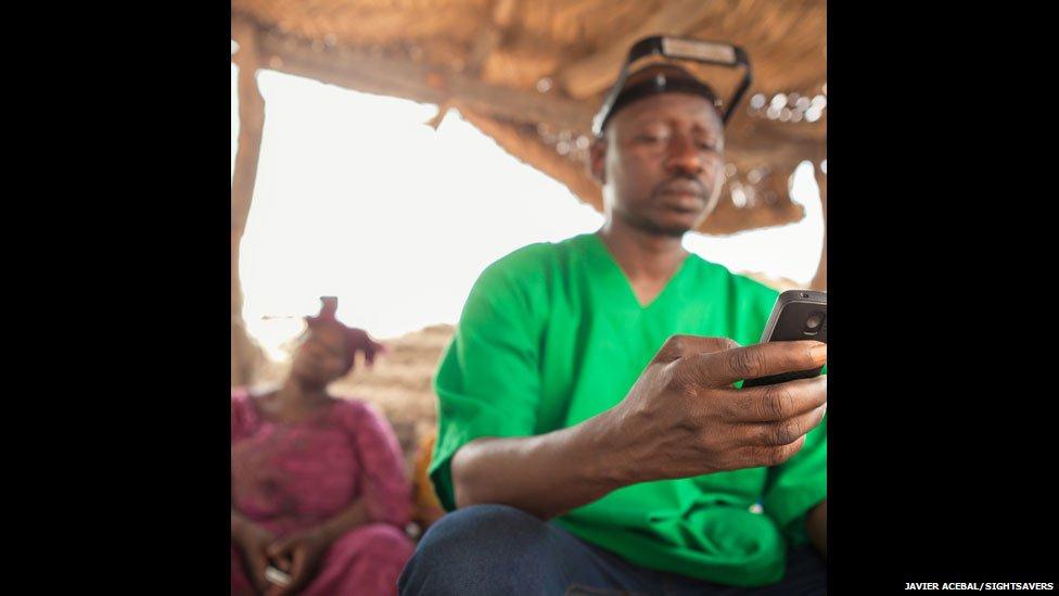 Eye surgeon Boubacar Fomba uploading information on a mobile phone