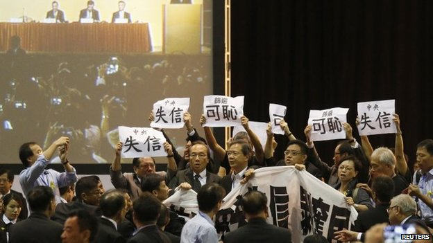 Pro-democracy lawmakers hold up a banner and signs during a protest as Li Fei (seen on screen), deputy general secretary of the National People's Congress (NPC) standing committee, speaks during a briefing session in Hong Kong, 1 September 2014