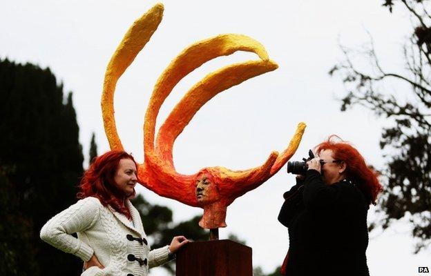 A woman has her photograph taken beside a sculpture in Ireland's National Botanic Gardens