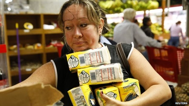 A woman grabs packages of corn flour at a supermarket in Caracas (21 August 2014)