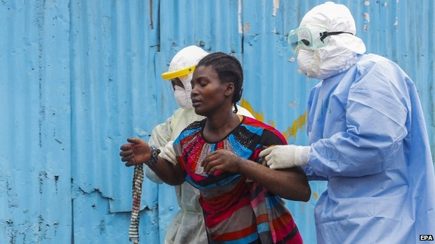 Liberian nurses escort a suspected Ebola patient into the John F. Kennedy (JFK) Ebola treatment centre in Monrovia (18 September 2014)