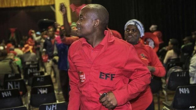 An Economic Freedom Fighters' supporter sings and dances as he attends a vigil in support of the party's leader Julius Malema on the eve of his trial on charges of corruption on September 29, 2014 in Polokwane.