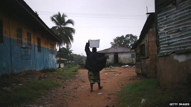 A resident in New Kru Town, Liberia, walks through the deserted streets - October 4, 2014