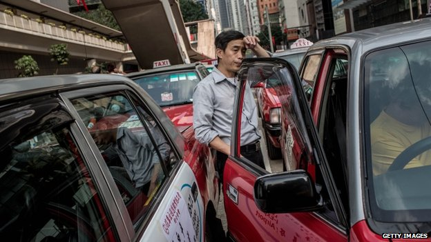 A taxi driver in Hong Kong waits by his car during a protest against roadblocks by demonstrators