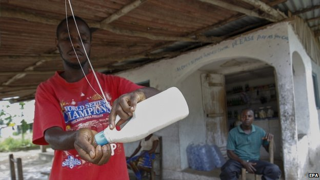 A Liberian man washes his hands from a water bottle tied to a roof outside a shop to curb the spread of Ebola in Dolos Town Community, Margibi County (9 October 2014)