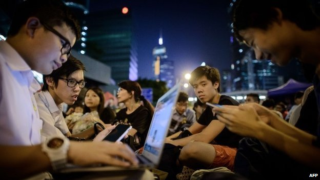 Students check their laptops and smartphones during a rally of pro-democracy demonstrators in Hong Kong - 10 October 2014