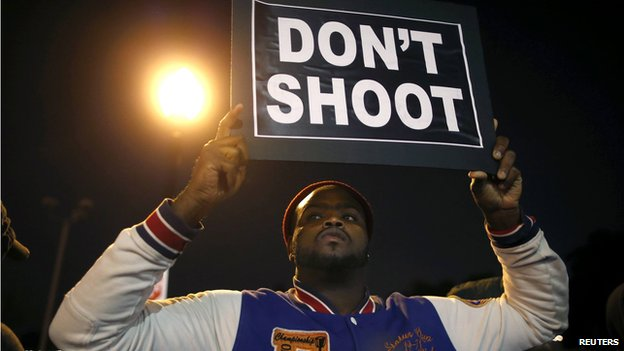 A protester holds up a sign across the street from the police station during a protest in Ferguson, Missouri October 10, 2014