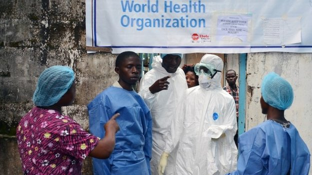 Health workers in protective gear pose at the entrance of the Ebola treatment unit of the John F Kennedy Medical Center, in the Liberian capital Monrovia