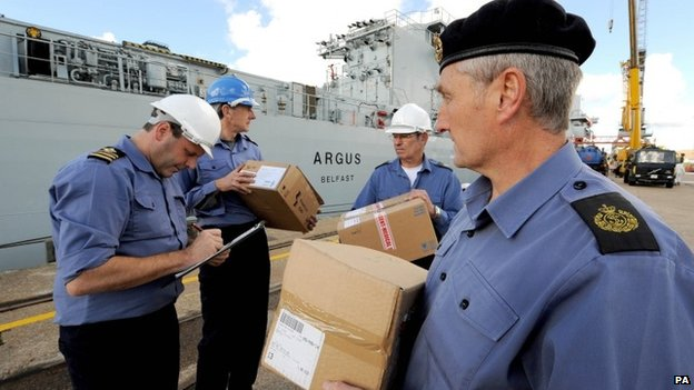 Undated picture issued by MoD showing RFA Argus's Chief Officer Shane Wood (left) checking the first load of supplies for its deployment to Sierra Leone