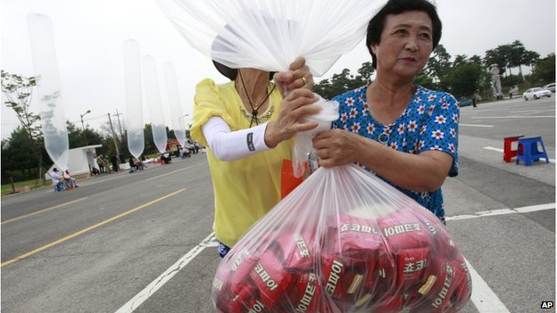 North Korean defectors carry to release a balloon to let it fly to the North, carrying chocolate pies and cookies during a rally against the North's recent threat at the Imjingak Pavilion near the border village of Panmunjom (DMZ) that separates the two Koreas since the Korean War, in Paju, South Korea, Wednesday, 30 July 2014.