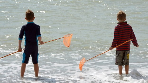 Boys standing in the sea.