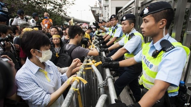 A pro-democracy protester ties up a yellow ribbon to one of the fences blocking the access to Liaison Government Office during the rally in Hong Kong (9 November 2014)