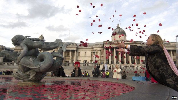 A lady throws poppies in to the fountain in Trafalgar Square on Armistice Day 11 November 2014