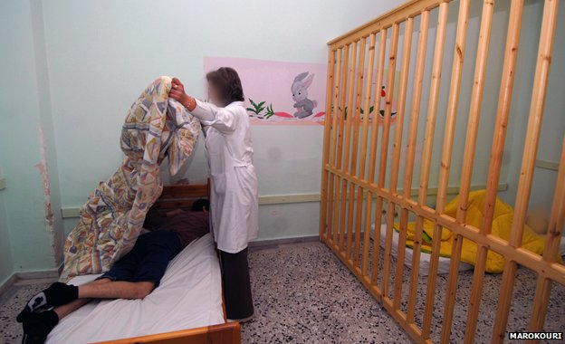 Wooden bars separate part of a room - a person lies behind the bars and a woman puts a cover over someone lying on a bed, 2008