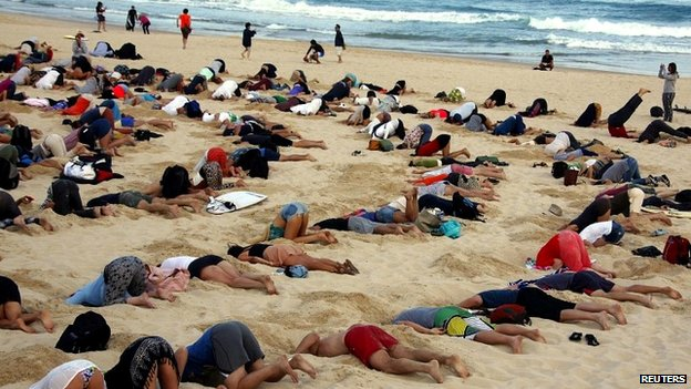 The group of demonstrators take part in a protest by burying their heads in the sand at Bondi Beach - 13 November 2014