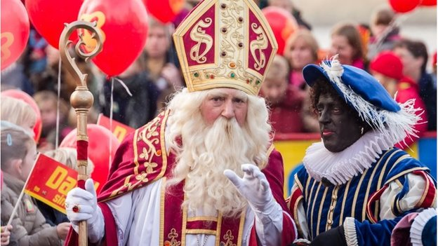 Actors dressed as Saint Nicolas, left, and Black Pete greet children in Antwerp, Belgium on Saturday Nov 15