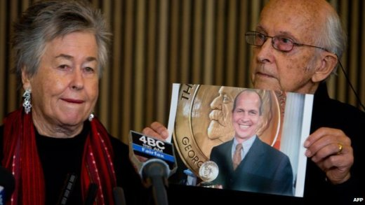 Juris Greste (R) displays a picture of his son, jailed Australian Al-Jazeera journalist Peter Greste, next to his wife Lois (L) during a press conference in Brisbane on June 24, 2014.