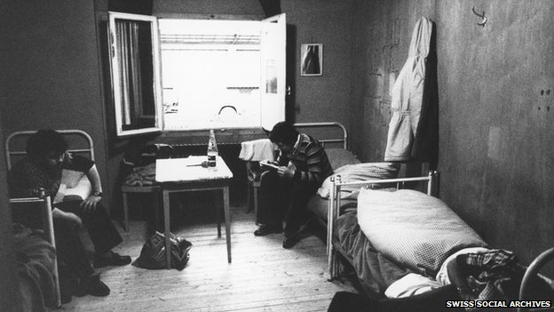 File photo of seasonal workers in Switzerland sitting on their beds reading from Unia's exhibition 'Baracken, Fremdenhass und Versteckte Kinder'