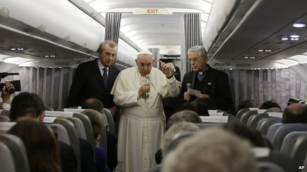 Pope Francis flanked by Vatican spokesman father Federico Lombardi talks to journalists during a press conference aboard the flight towards Rome