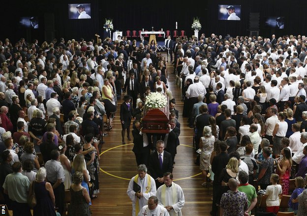The coffin of Hughes is carried down the aisle at Macksville High School