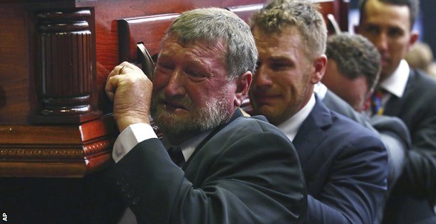 Gregory Hughes, father of Phillip, helps carry his son's coffin