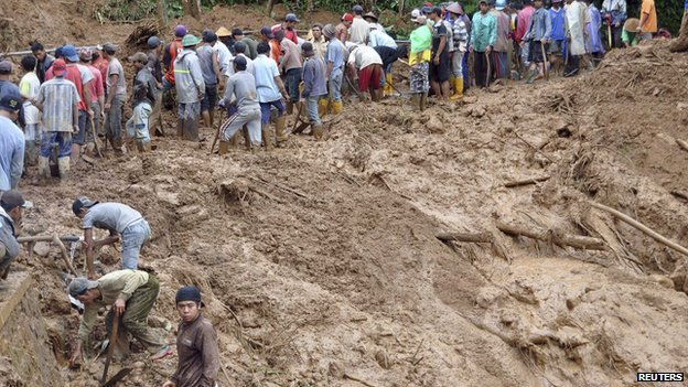 Villagers use shovels to remove mud from the main road at Pasuruhan village in Wonosobo December 12, 2014, in this photo taken by Antara Foto
