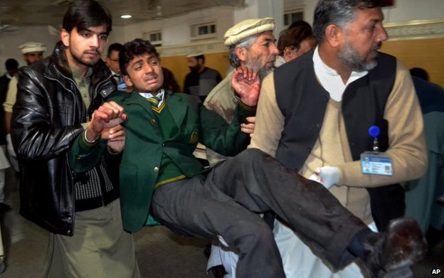 Pakistani volunteers carry a student injured in the shootout at a school under attack by Taliban gunmen, at a local hospital in Peshawar, Pakistan. 16 December 2014
