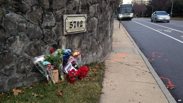 Flowers and messages are shown at the scene of a fatal collision between a car and bicyclist along a Baltimore residential street with a bike lane 29 December 2014
