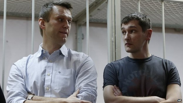 Russian opposition activist and anti-corruption crusader Alexei Navalny, 38, left, and his brother Oleg Navalny stand at a court in Moscow, Russia, Tuesday, Dec. 30, 2014