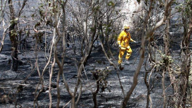 Firefighters work to mop up a fire near Mia Mia in Victoria, Australia, 18 December 2014