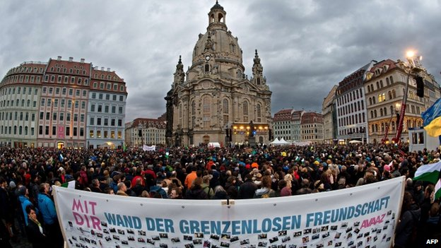 "A banner reading ""Wall of friendship without borders"" can be seen in the foreground as thousands of people take part in the Dresden rally (10 January 2015)"