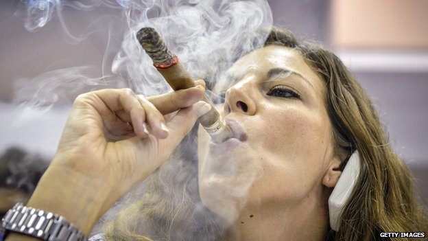 Woman smokes Cuban cigar at cigar festival in Havana  on 27 February 2014