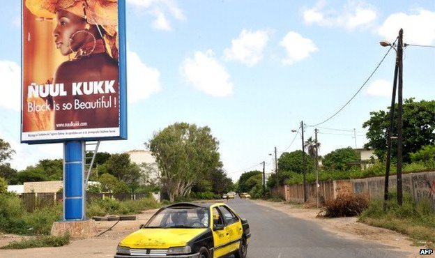 A taxi passes by a Nuul Kukk ('All Black') citizen's movement poster which reads 'Black is so Beautiful!' - October  2012 in Dakar, Senegal
