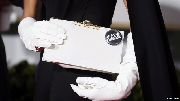 "Amal Clooney poses with handbag which has a button badge slogan reading ""Je suis Charlie"""
