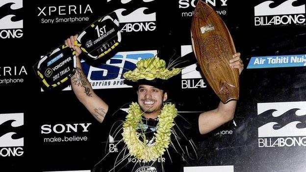 Brazilian surfer Ricardo Dos Santos holding a trophy on 14 August 2012