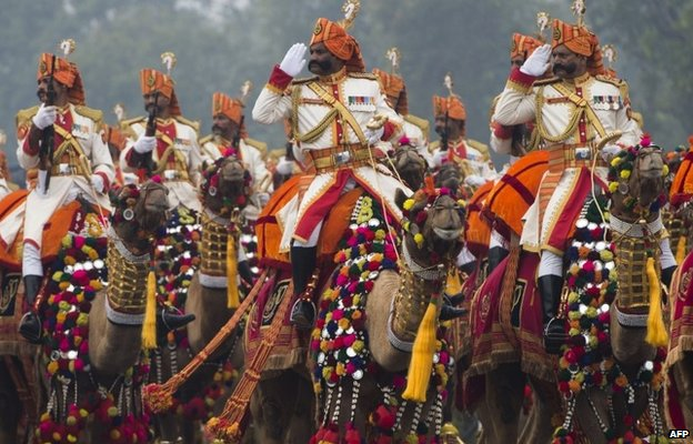 Indian military personnel salute while riding camels during the Republic Day Parade in Delhi on January 26, 2015