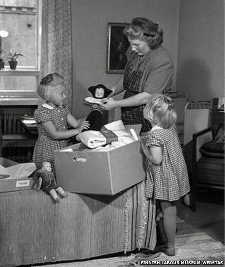 Mother and daughters look at a pack from 1947