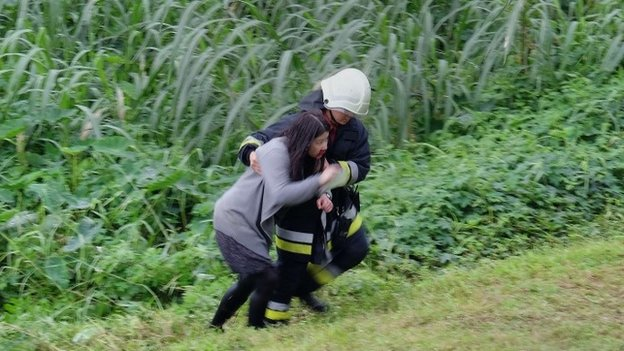 An injured passenger is escorted up the river bank by one of the rescue workers