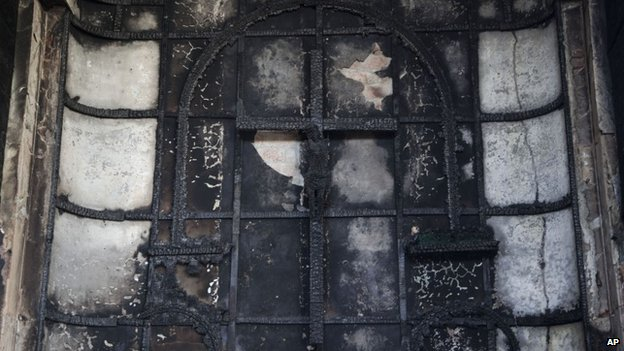 "A burnt crucifix stands at the altar of St. Sebastian""s Church after a fire destroyed the church on Monday, in New Delhi, India, Tuesday, Dec. 2, 2014."