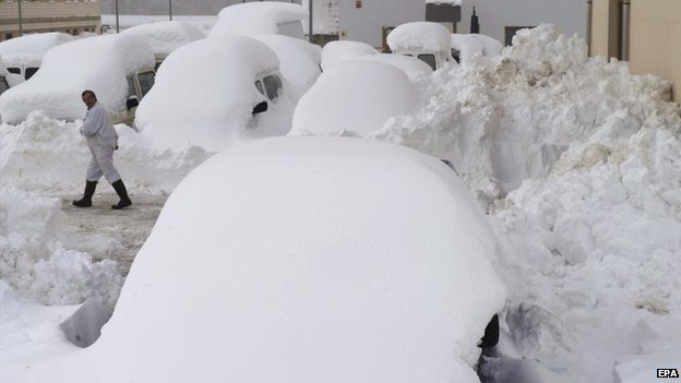 A man walks among cars covered in snow in Burguete town, Navarre region, northern Spain, 4 February 2015.