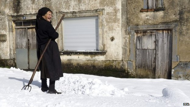 An elderly woman holds a rake at the entrance to her home after heavy snowfall in the small village of O Cavado in Galicia, north-western Spain, 4 February 2015.