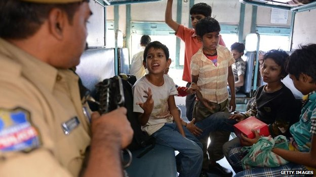 A rescued Indian child labourer gestures to a policeman while on board a Patna-bound express train at a railway station in Secunderabad on 5 February