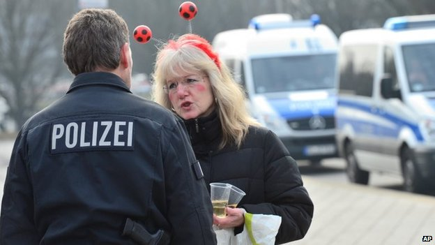 A woman dressed up for carnival talks to a policeman in Braunschweig, Germany, Sunday after the annual carnival procession was cancelled shortly before it was due to begin over fears of a terrorist attack
