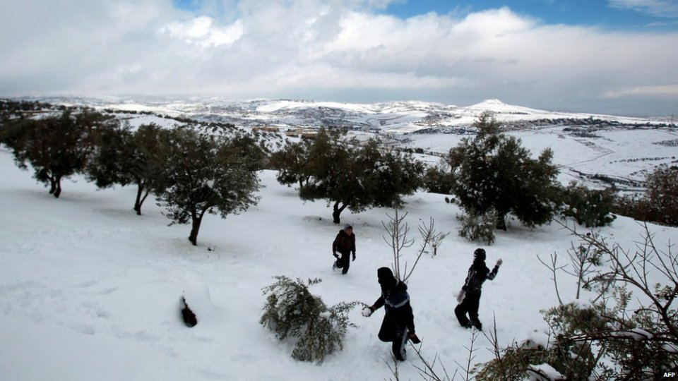 Palestinian children play in the snow in the village of Tuqu' near the West Bank city of Bethlehem on Friday