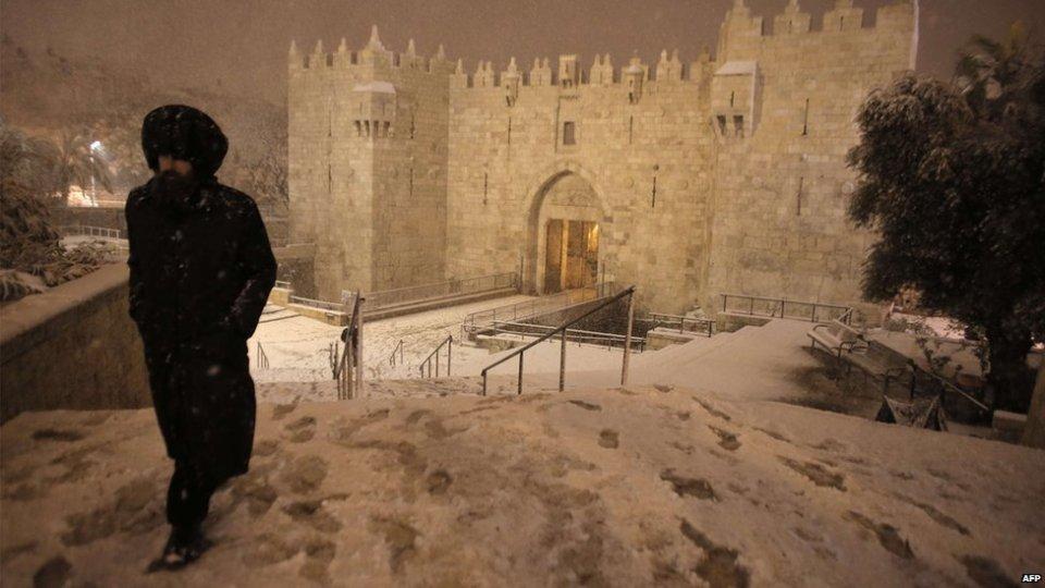 An ultra-Orthodox Jewish man walks near Damascus Gate in Jerusalems Old City as snow falls